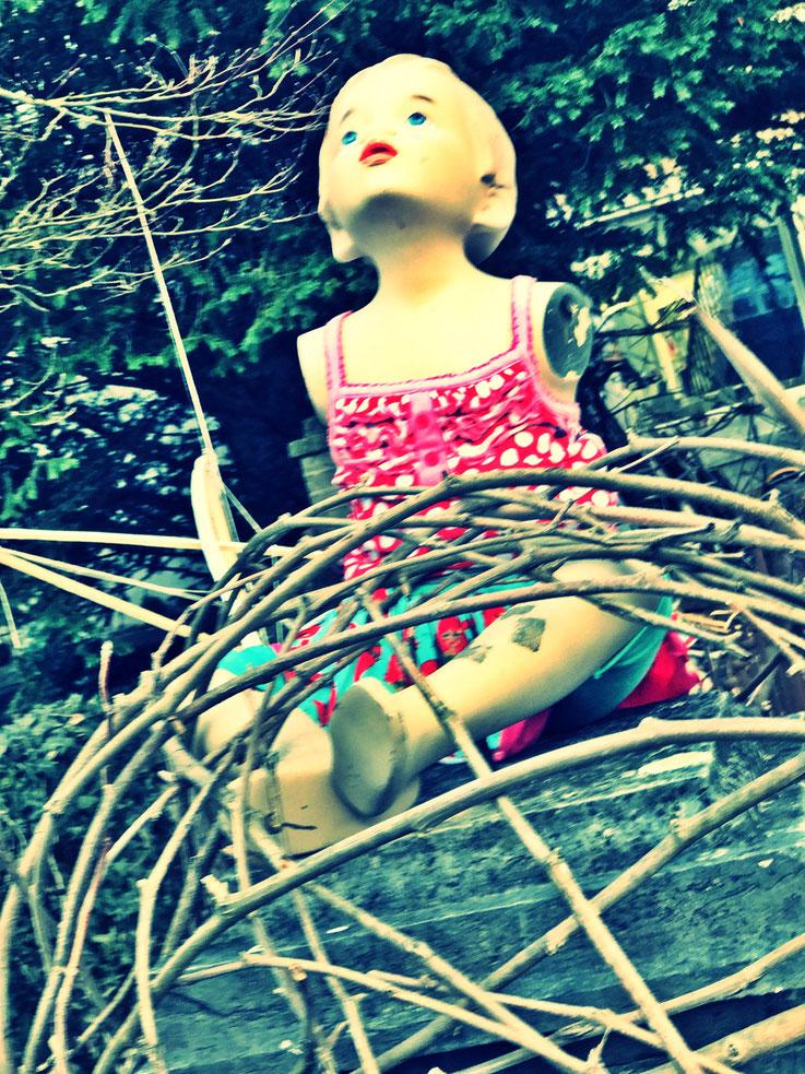 Pedro Meier – Puppe in rotem Kleid – Frühlingserwachen – Garten Künstlerhaus S11 Solothurn – PhotoArt by © Pedro Meier Multimedia Artist / Smoke Performer, Atelier Gerhard Meier Weg Niederbipp /Bangkok / Kunsthalle Olten Visarte DADA FLUXUS, SIKART Zürich