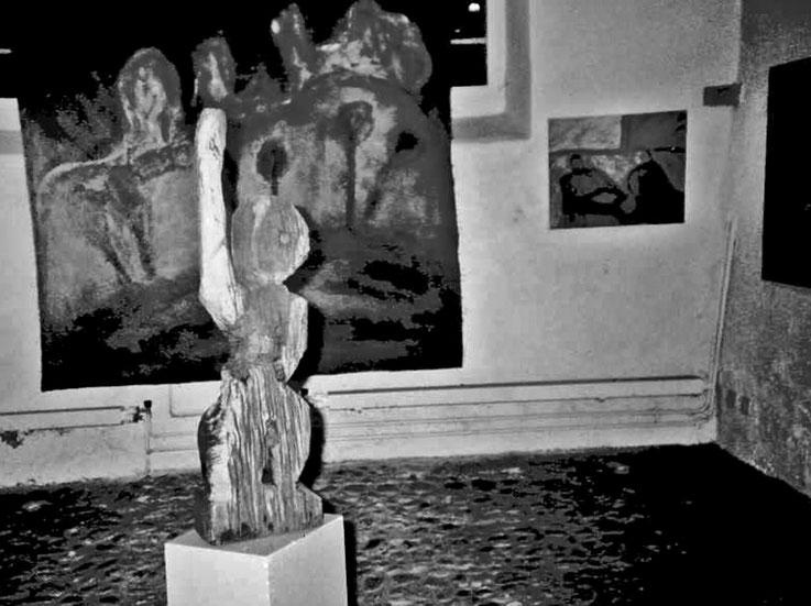Pedro Meier – »Eisenbahner« Skulptur 1987, Eichenholz alte Eisenbahnschwelle – Galerie Bremgarten – im Hintergrund Ölbild auf Jute – Atelier: Gerhard Meier-Weg Niederbipp und Bangkok – Kunsthalle Olten Offspace – Visarte FLUXUS DADA DigitalArt – SIKART ZH