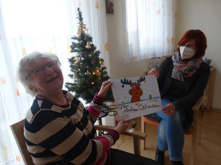 Für einen kurzen Moment hat die Seniorin Maria Müller (links) ihre Maske abgelegt, um freudestrahlend das Bild der Schülerschaft aus der HerzogOtto-Mittelschule von Pflegedienstleiterin Birgit Baier (rechts) zu erhalten.