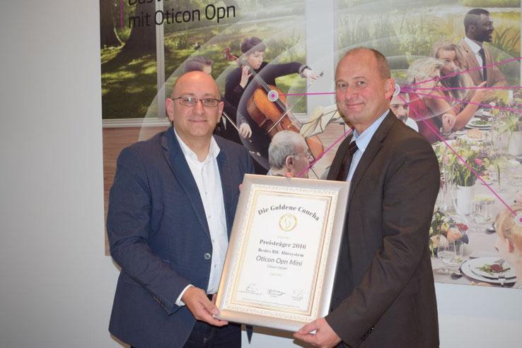 Oticon Geschäftsführer Torben Lindoe (re.) und IAS Geschäftsführer Jürgen Leisten (lks.) bei der Übergabe der Siegerurkunde auf der EUHA in Hannover.