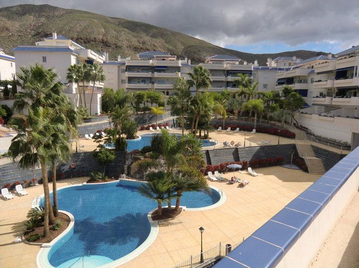 Blick vom Penthouse auf die Poollandschaft in Palmen eingebettet.