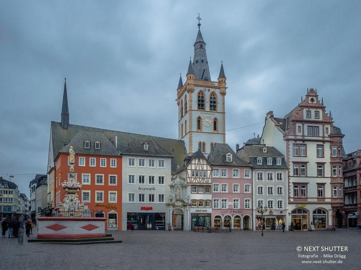 Marktplatz in Trier mit dem Turm der Marktkirche St. Gangolf, links im Vordergrund die Petrussäule.