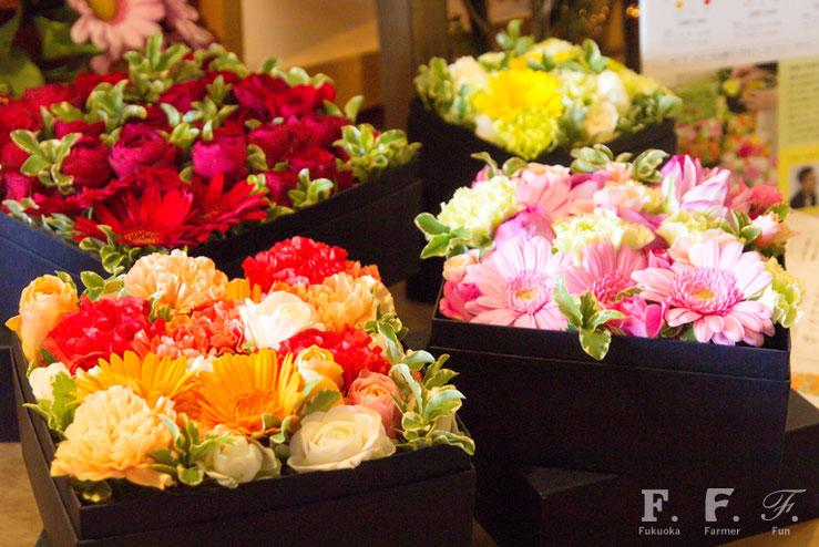 華やかに陳列されたボックスフラワー、箱の中のお花の色で赤・ピンク・オレンジ・白の4種類があります