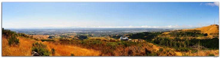Panoramasicht von Christchurch mit Bergen im Hintergrund und blauem Himmel.