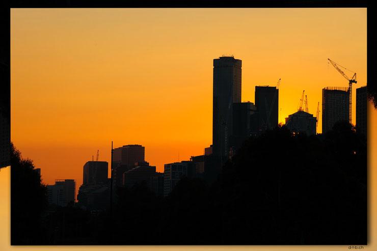 Schwarze Skyline der Stadt Melbourne am Abend mit orangem Himmel.