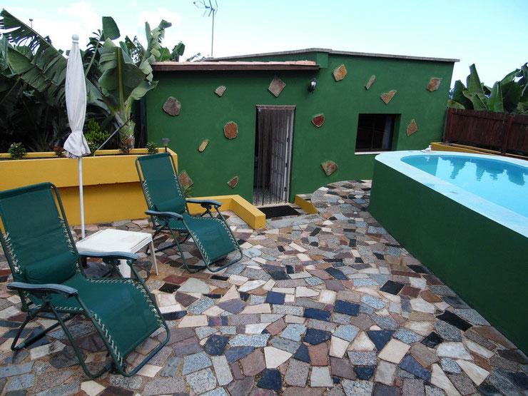 Blick auf das Haus mit Pool und an der linken Seite sieht man den Bereich zum Sonnen. Im Hintergrund sind nur Bananen zu sehen.