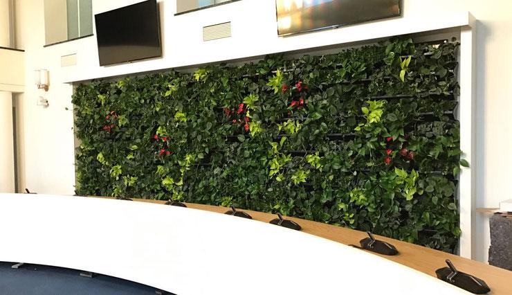 jardín vertical interior plantado con epipremnum y anturium en una gran sala de conferencias