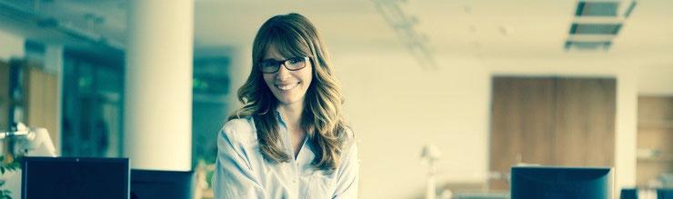 28jährige Frau mit langen, brünetten Haaren und dunkler Brille die freundlich lächelt. Sie lehnt an einem Tisch in einem Großraumbüro.