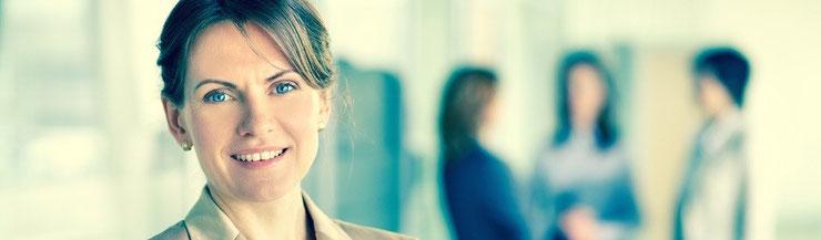 """32jährige Frau mit dunkleren Haaren die sie im Nacken zusammen gebunden trägt. Hat blaue Augen und lächelt. Sie trägt eine beigen Blazer und im Hintergrund stehen 3 weitere """"Business-Frauen"""" und sprechen miteinander."""