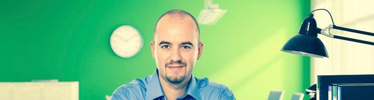 Junger Mann mit Vollbart und Halbglatze am Schreibtisch vor einer grünen Wand