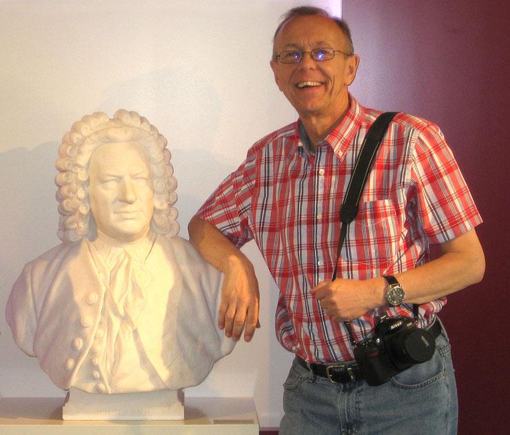 Peter Bach jr. (rechts) steht vor einer Johann-sebastian-Bach-Büste (links). Er lehnt sich auf die Schulter der Büste auf. Im Hintergrund ist eine weiße-rote Wand zu sehen. Peter Bach jr. hat eine Kamera über der Schulter hängen.
