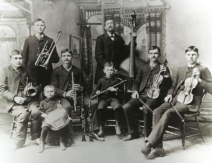 Man sieht auf einem schwarz/weißen historischen Motiv die Bach-Band: sechs Söhne sitzen, der VAter und ein Sohn stehen dahinter. Jeder hat ein Instrument. Alle schauen ernst zur Kamera.