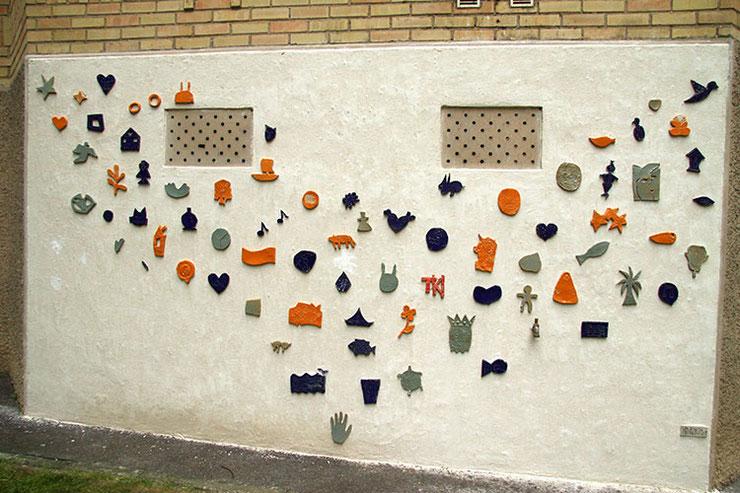 Portion de mur réalisée en 2013 (première partie). Les pièces émaillées ont été collées par le public, la maçonnerie de finition n'a pas encore été faites.