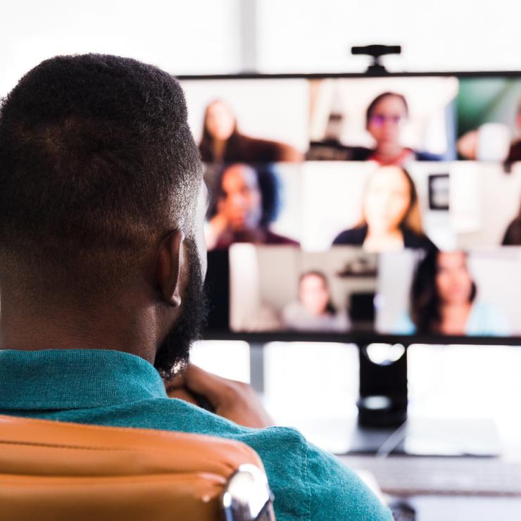 Videokonferenz: Blick auf Mitarbeiter von hinten und Bildschirm mit virtuellen Teilnehmern