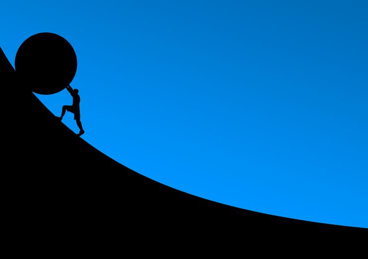 Ein Mann schiebt etwas auf den Berg, es geht mit der Krankheit bergauf