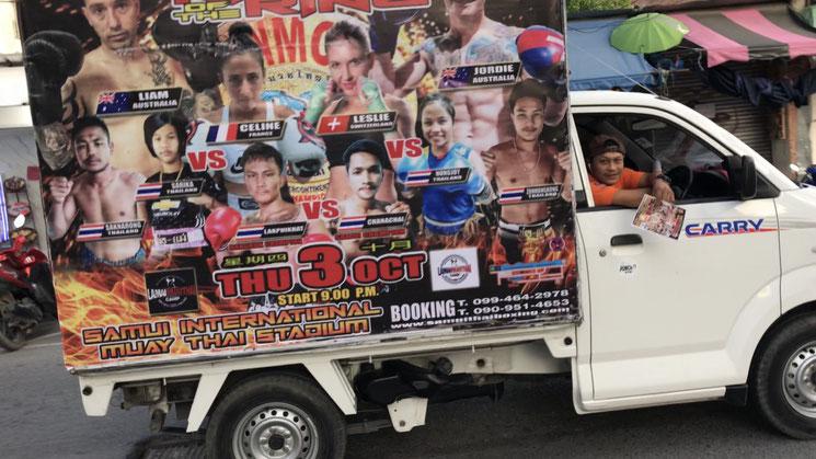 Ein Pick-Up mit Werbeplakaten für eine Muay Thai-Wettkampfveranstaltung.