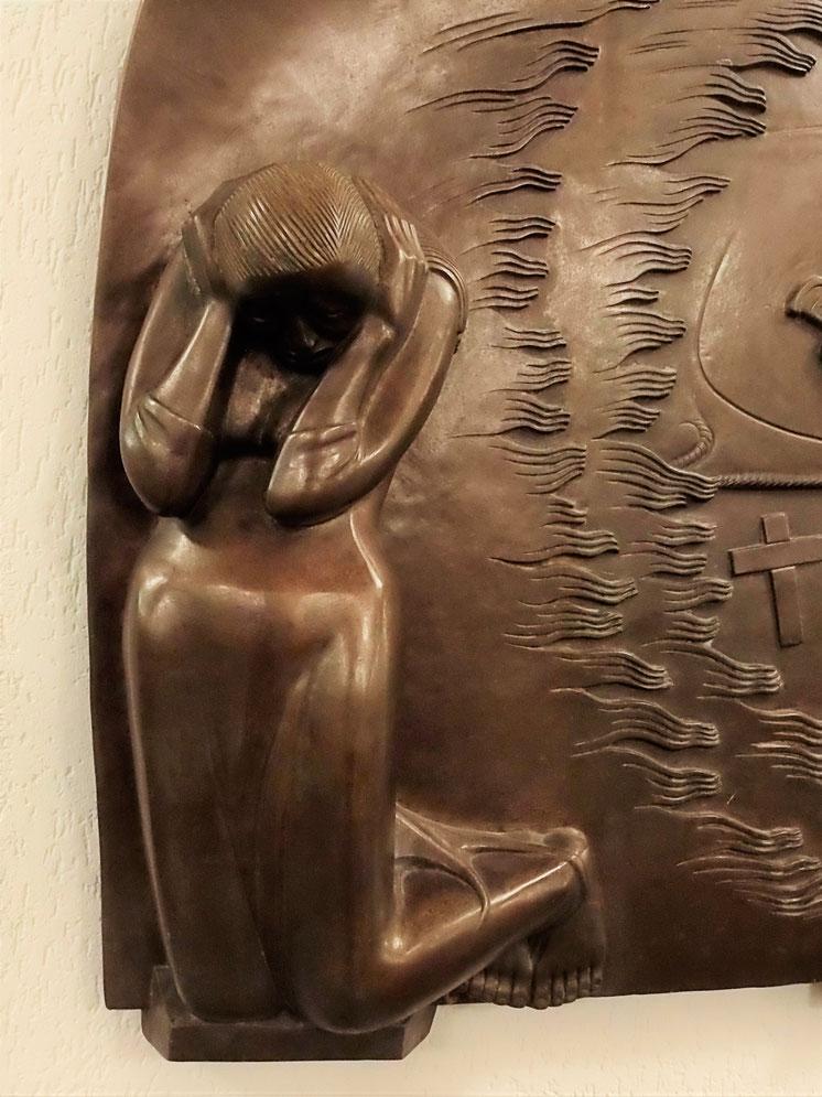 Eine Frau kniet auf der Erde. Sie hat beide Hände über den gesenkten Kopf geschlungen.
