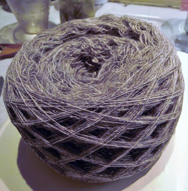 Weiß-grau melierte Wolle zu einem rundem Kneul gewickelt