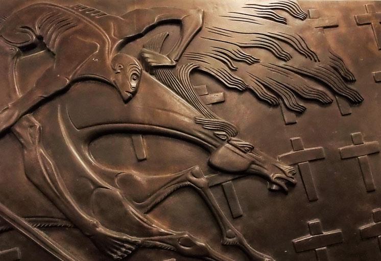 Ein nackter, abgemargerter Reiter mit Schwert in der Hand fliegt mit seinem Pferd über die Kreuze eines Friedhofes.