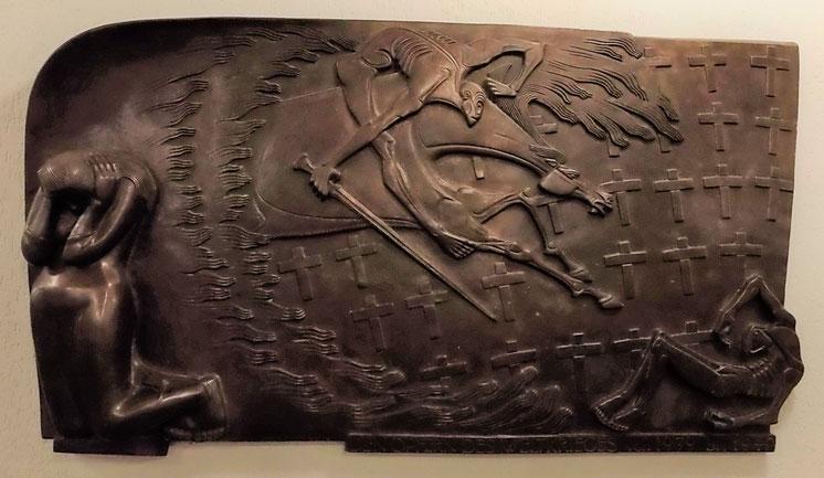 Darstellung der gesamten Bronzeplatte. Links kniet die Frau, rechts liegt die tote Gestalt zwischen den Kreuzen und über allen fliegt das Pferd mit dem Reiter mit Schwert.