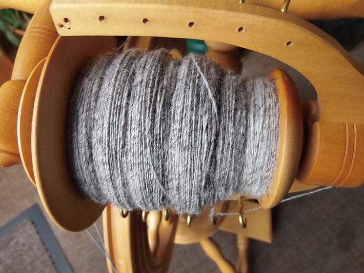 Weiß-grau melierte Wolle auf einer Spindel gewickelt
