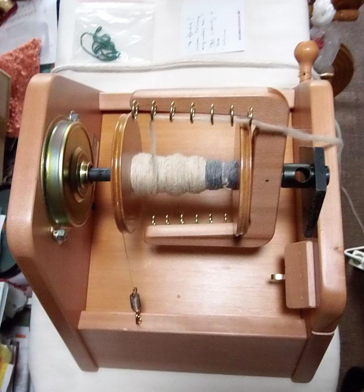 Spinnrad mit einer Spindel deren Achse durch einen Elektromotor angetrieben wird.