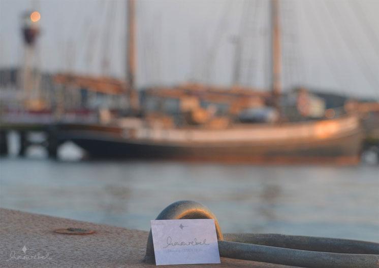 honourebel Slow Fashion. Business Card bei Sonnenuntergang am Segelhafen in Kiel mit Schiff im Hintergrund.