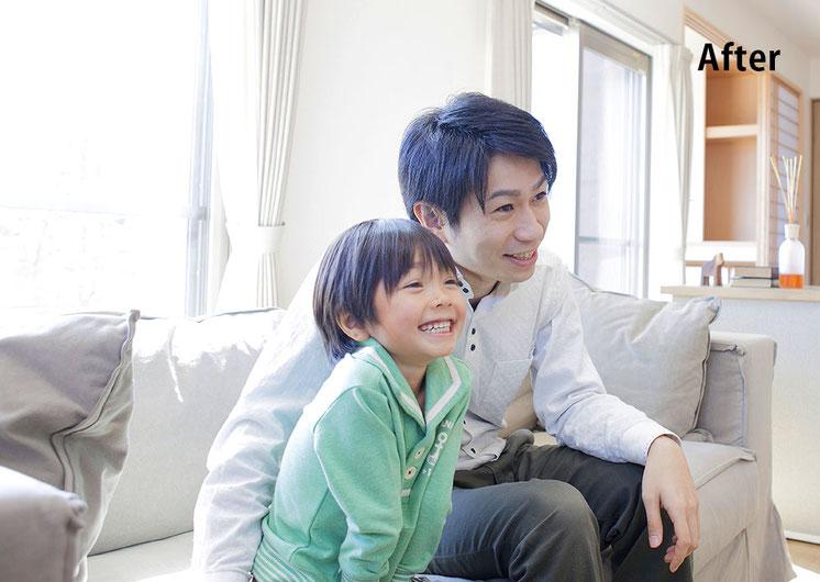 ソファで楽しそうに一緒にテレビを見る父と息子