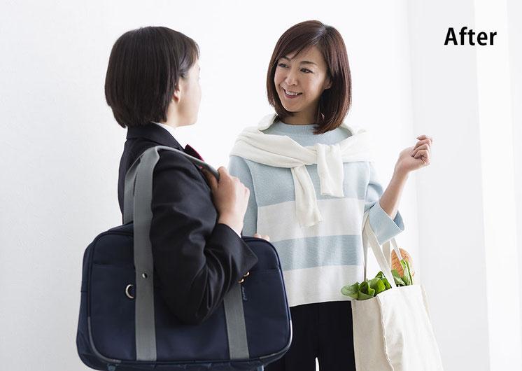 玄関で笑顔で立ち話をする買い物帰りの母親と学校帰りの娘