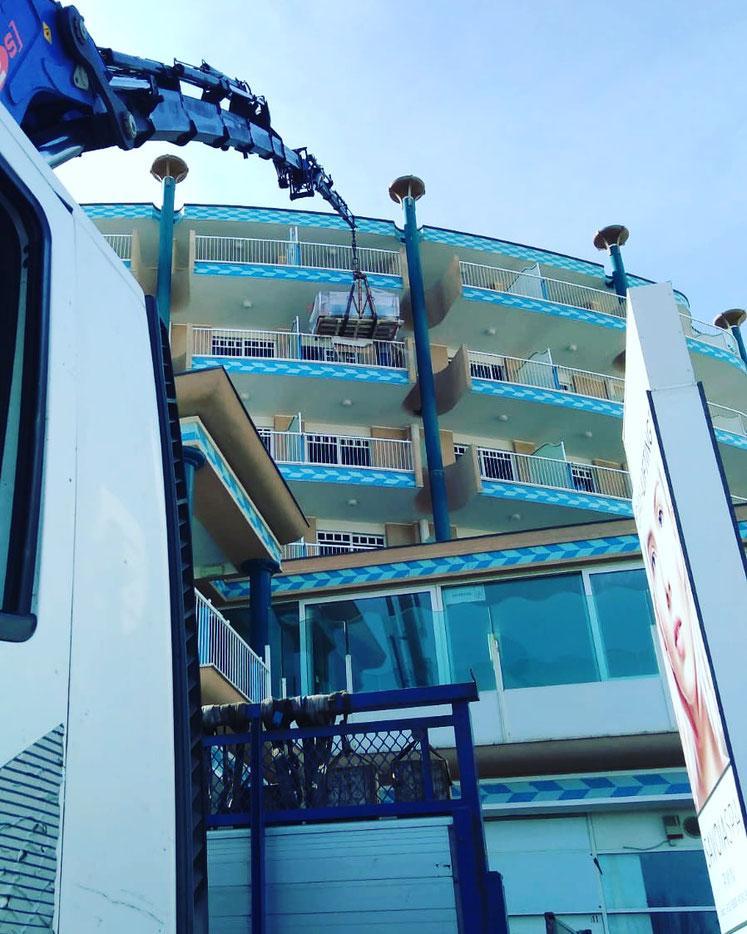 Camion gru per sollevamento materiale su albergo a Rimini