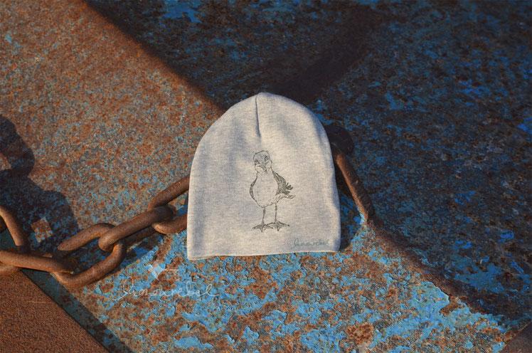 honourebel Slow Fashion. Hochwertiger, weicher Hoodie mit Möwendruck für Kinder in blau meliert und weiss aus 100 % Biobaumwolle bei Sonnenuntergang am Segelhafenhafen.