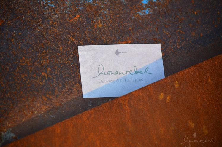 honourebel Slow Fashion. Business Card auf rostigem Hintergrund bei Sonnenuntergang am Segelhafen.