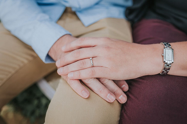 A couple holding hands showing off her engagement ring