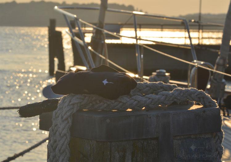 honourebel Slow Fashion. Hochwertiges, weiches Polo Shirt, navy mit weißem Rochen Stick bei Sonnenuntergang am Segelhafen in Kiel.