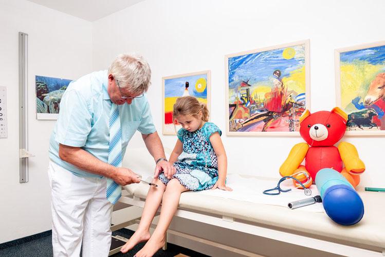 """Die neuropädiatrische Untersuchung besteht aus zahlreichen Schritten. Ein wichtiger Bestandteil ist die Untersuchung der Reflexe. Auf dieser Abbildung ist die Prüfung des """"Patellarsehnenreflexes"""" gezeigt."""