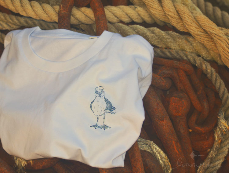 honourebel Slow Fashion. Hochwertiges, weiches T-Shirt in weiß mit kleiner, lächelnder Möwe auf der Brust in blaugrau aus gang am Segelhafenhafen in Kiel.