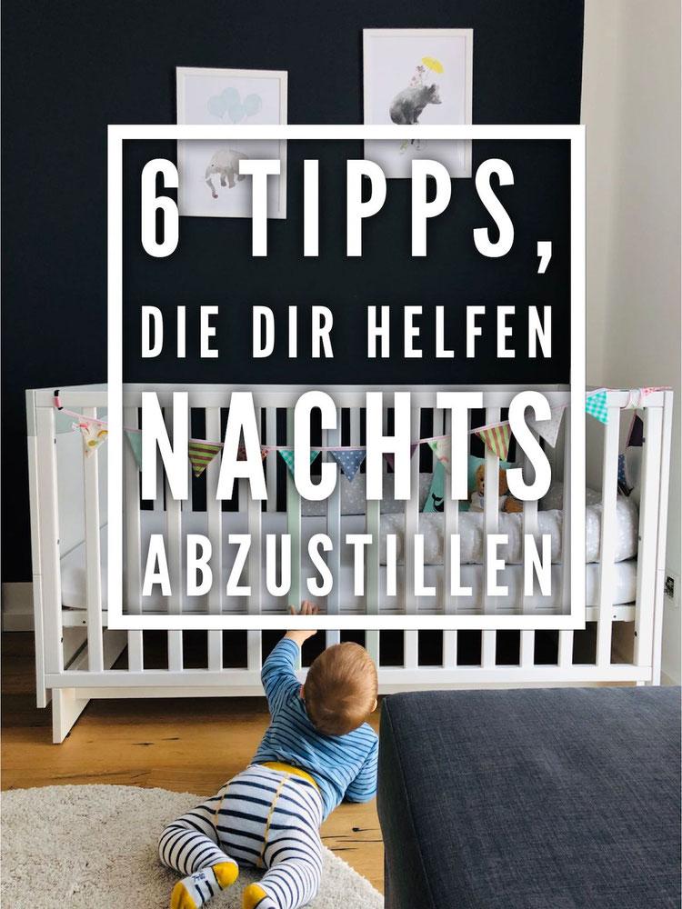 Baby alleine im Kinderzimmer am Babybett mit Wimpelkette; 6 Tipps zum Abstillen nachts