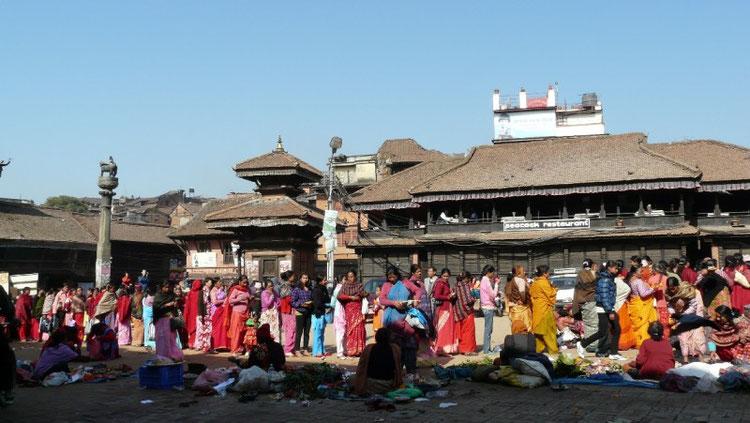 Longue queue au temple principal de Bakthapur (une des trois villes royales de la vallee de Kathmandou). Drapees dans leur saris colores les femmes viennent deposer leur offrandes (fruits, oeufs, fleurs, bougies..)