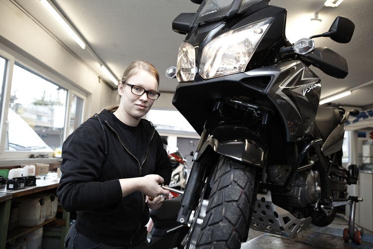 KfZ-Werkstatt: Mädchen schraubt am Motorrad