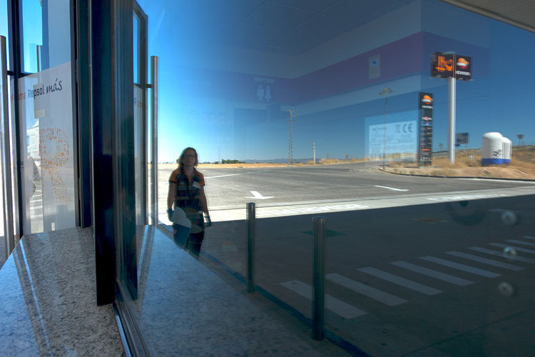 Mathieu Guillochon photographe, sur la route, autoroute, couleurs, station service, conteneurs, Espagne, reflet, repsol, employée féminine