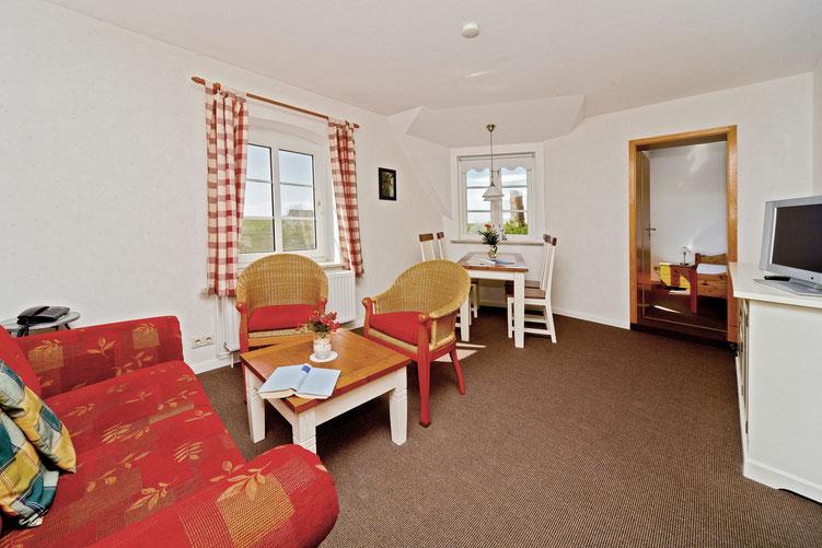 Gemütliches Wohnzimmer in der Wohnung Hooge mit Aussicht zur Alten Kirche und zum Deich