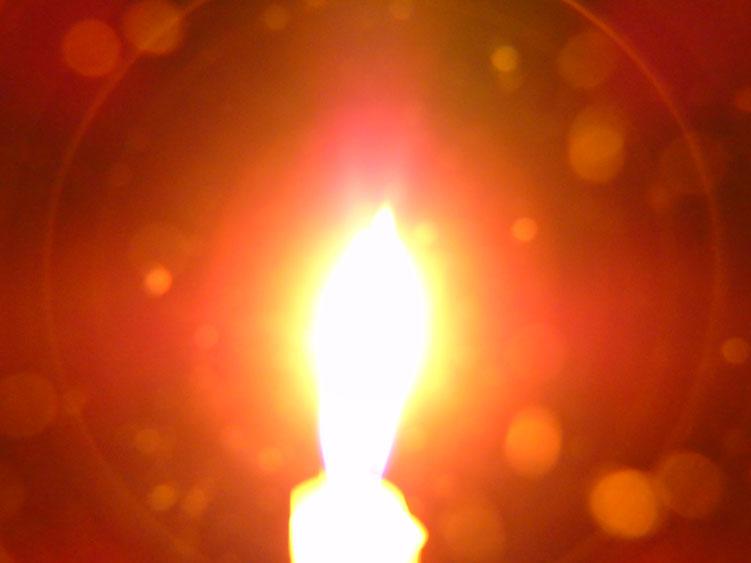 Eine kleine weiße Kerze erstrahlt bei geöffnetem Herzen/ Quelle: www.lichtwesenfotografie.com