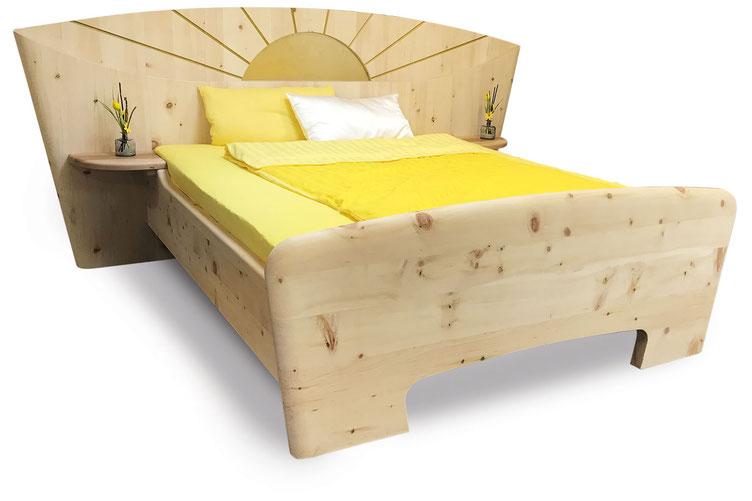 """Zirbenholzbett """"Morgensonne"""", eingefräste, golden lackierte Sonne im Kopfteil, Kopfteil oben bogenförmig, seitliche Ablagen"""