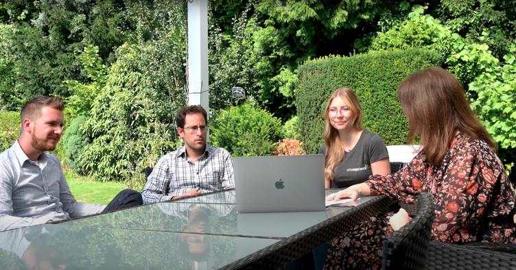 Alex, Lothar, Celina und Sarah im Bürogarten am Tisch.