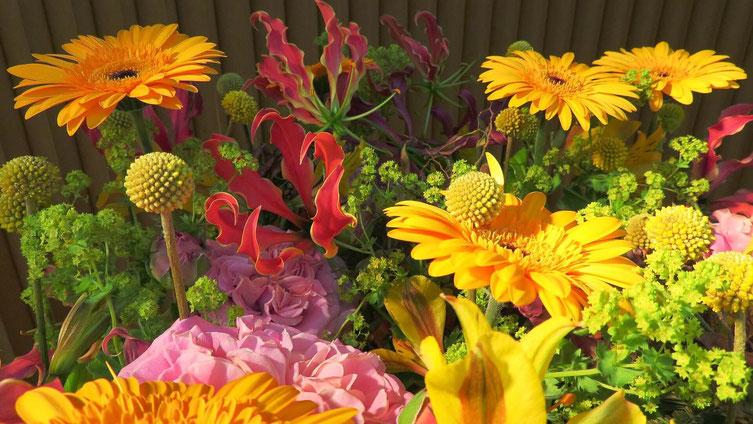 Exotisch wird dieses Blumengesteck durch die rote Ruhmeskrone. Ebenfalls im Trend der grün-gelbe, runde Trommelstock.