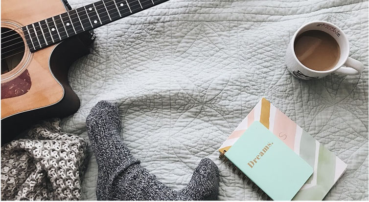 Feet in wool socks on a bed with a guitar, cup of coffee, journal and cozy-looking blanket