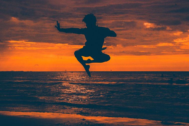 Eine Silhouette eines Taido-Kämpfers, der am Strand in die Luft springt. Im Hintergrund sieht man das Meer bei untergehender Sonne.