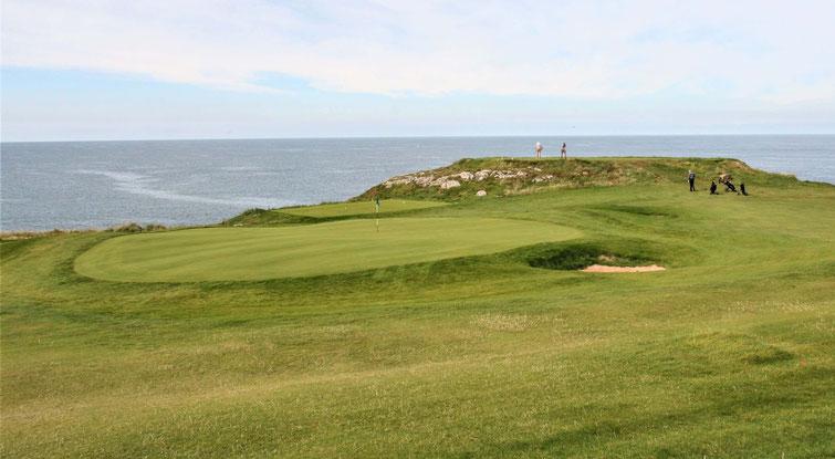 Putting Green des Nefyn Golfplatzes in Wales im Vorgergrund, im Hintergrund das Meer