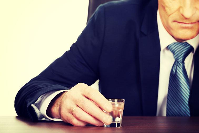 Mann im Anzug trinkt am Schreibtisch ein Glas Wodka; Detektive der Kurtz Detektei Hannover