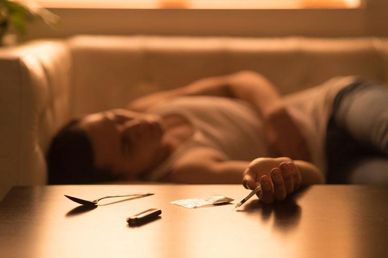 Junger Mann liegt auf Couch, eine Spritze in der Hand und Drogenbesteck auf dem Tisch; Drogenabhängigkeit in Bochum, Detektive ermitteln